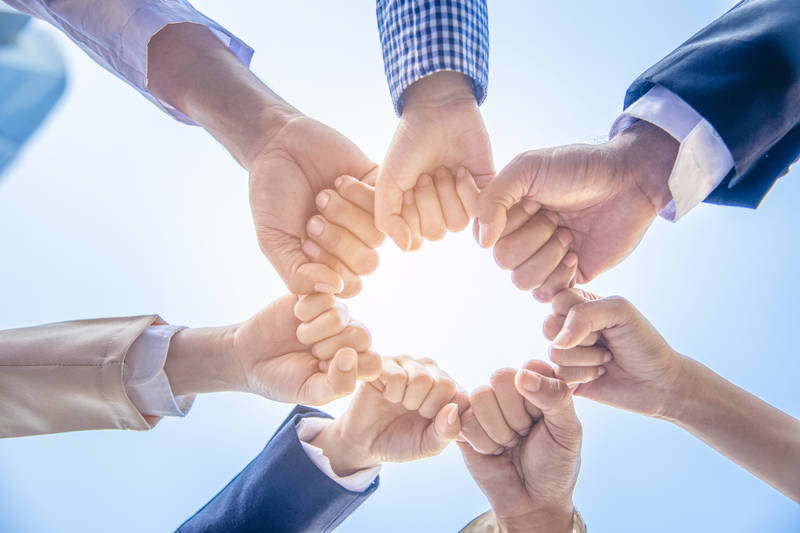 business people with fists together in a circle to show trust